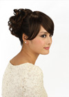 This hairpiece is absolutely gorgeous. It is a very classy updo which is so chic and romantic. The hair is curly and brushed up all around to create this high do.